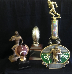 Resin running-18.25 Gold football with wood base-27.50 Trophy with football player 12 inch- 12.95 Resin with brown ball-10.50    Green 11 inch Trophy-11.50 Green with soccer balls 12 inch trophy-12.50 Soccer ball trophy- 8.25 Resin Kicking ball- 13.50 Green 11 inch Trophy-11.50 Green with soccer balls 12 inch trophy-12.50 Soccer ball trophy- 8.25 Resin Kicking ball- 13.50 Burst thru oval 8 inch-13.50